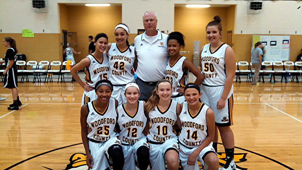 """8TH GRADEERS HONORED. The Woodford County Middle School honored its eighth-grade girls' basketball team on """"8th Grade Night, prior to its game against Georgetown at home on Thursday, Sept. 22. Shown in the photo are, front row, from left, Kamari Black, Halle Hood, Alyssa Hysell, and Caegan Brandenburg; back row, Adriana Jackson, Devan Champion, Stephen Bruce (head coach), Asia Shands, and Lilli Bicknell. (Photo submitted)"""