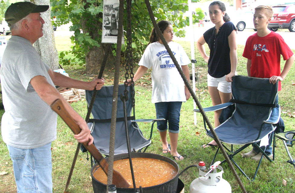 BURGOO CHEF Rick Caudle had hungry customers of all ages at the 36th annual Hillbilly Daze in Millville Saturday, including, from left, Sydney Stanfield, Lauren Wingate and Nathan Mefford. (Photo by John McGary)