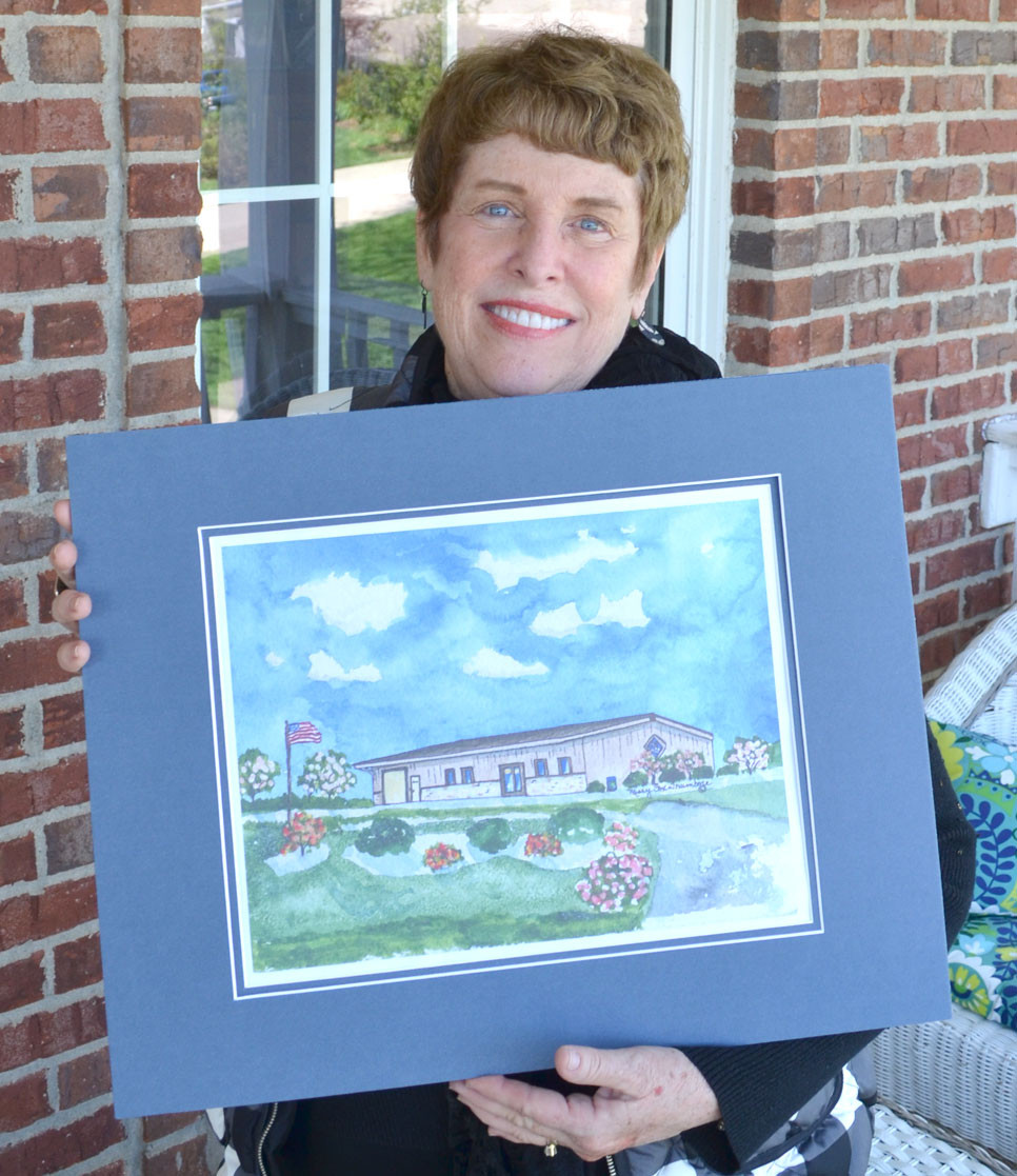 VERSAILLES ARTIST Missy Fox Trumbore stands with her painting of the Food Pantry for Woodford County, featured on thank-you cards that'll be sent to people who support the nonprofit's mission to feed the hungry. (Photo by Bob Vlach)