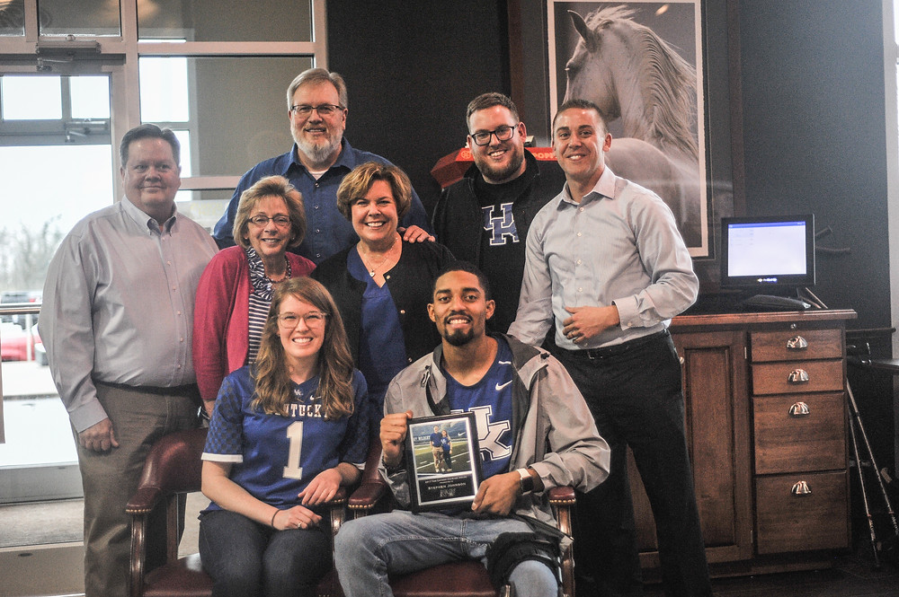 FORMER UK QUARTERBACK STEPHEN JOHNSON was awarded the first annual Tom Cannon Courage Award at a ceremony held at Jack Kain Ford on Wednesday, March 28. Pictured from left, Front row: Laura Cannon,Stephen Johnson. Middle row : Allan Cannon, Jane Cannon, Julie Cannon and Chris Cannon. Back Row: Jeff Eaton and Andrew Eaton. (Photo by Bill Caine)