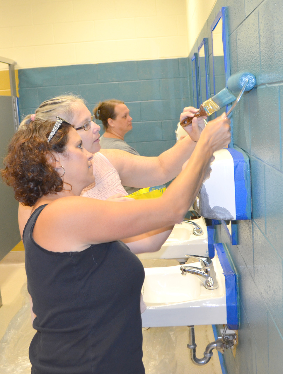TAMARA BRADLEY, foreground, worked alongside Dawn Staff, president of the Parent-Teacher-Student Organization, to repaint walls in the girls' bathrooms at Woodford County Middle School last Wednesday morning. Jaime Cheek is also pictured. (Photo by Bob Vlach)