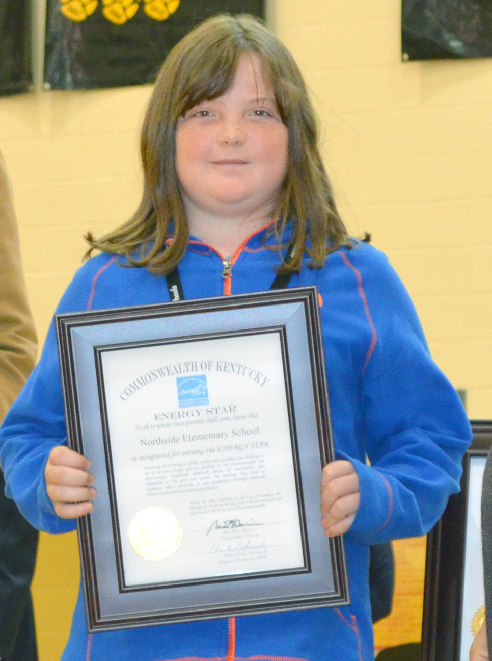 EMMA MULVIHILL, a fifth-grader at Northside Elementary, accepted her school's Energy Star certificate last Thursday, Oct. 20. All seven schools in the Woodford County Public Schools district are now certified as Energy Star Schools. (Photo by Bob Vlach)