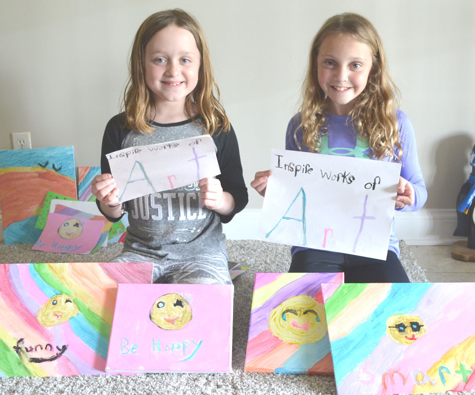 INSPIRE WORKS OF ART has given cousins Lillie Cowing, left, and Addison Moore an opportunity to express their creativity. The $50 generated from the sales of their artwork was recently donated to the Woodford Humane Society. (Photo by Bob Vlach)