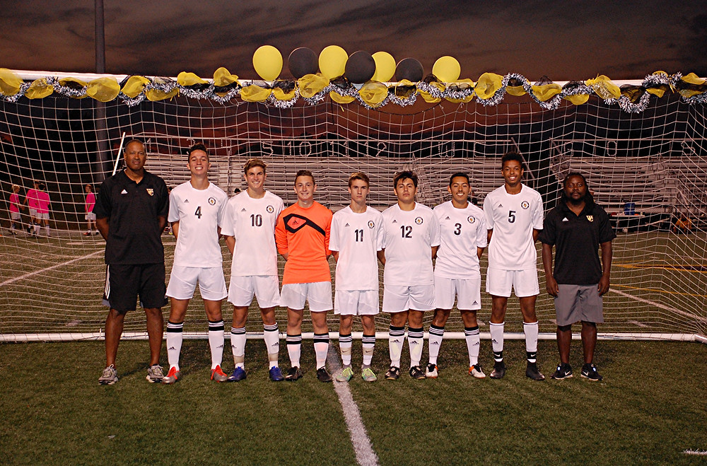 SENIOR CELEBRATION. The Woodford County High School boys' soccer team honored its senior players at home in Community Stadium on Tuesday, Oct. 4, prior to its game against Central Hardin. Standing with their coaches, assistant coach Mike Hayes, far left, and head coach Fonyam Atanga, far right, the seniors are, from left, Alex Karbach, Glenn Fister, George Stanley, Maclain Evans, Trevor Sparks, Jose Caloca and Trevor White. While both teams played hard, when the final horn sounded, the game ended in a scoreless tie. (Photo by Rick Capone)