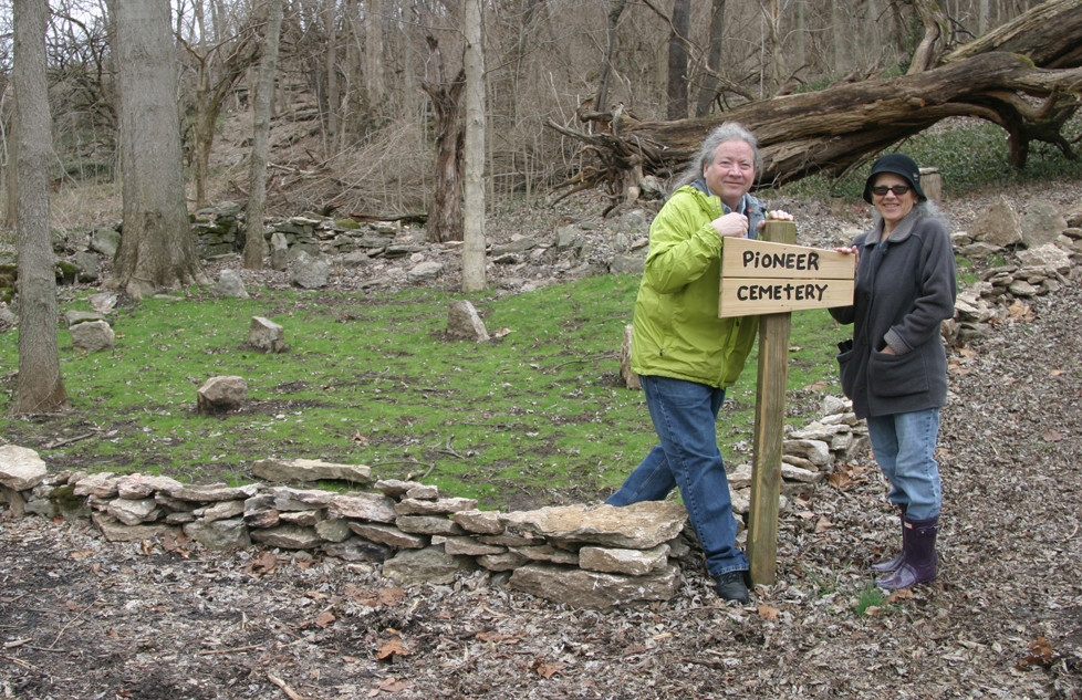 MIDWAY PARKS BOARD members John Holloway and Cecelia Gass show off some of the fruits of the labor of volunteers at Walter Bradley, Jr. Park: a sign marking the spot believed to have been a cemetery and the mulch-laid path of Cemetery Trail. (Photo by John McGary)