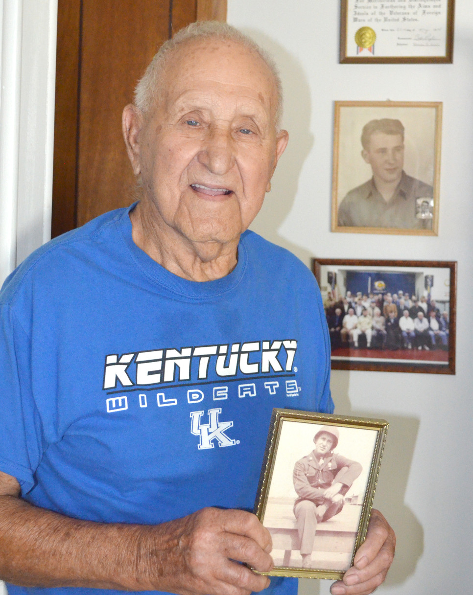WORLD WAR II VETERAN Mike Brown will likely be with his military brothers at the American Legion or VFW on July 4. Brown has a son, two granddaughters and one great-grandson. His family moved to Versailles when he was 2 years old. And he has lived his entire life - other than his three years of military service - in Woodford County. Brown is pictured with a photograph of his younger self at basic training. (Photo by Bob Vlach)