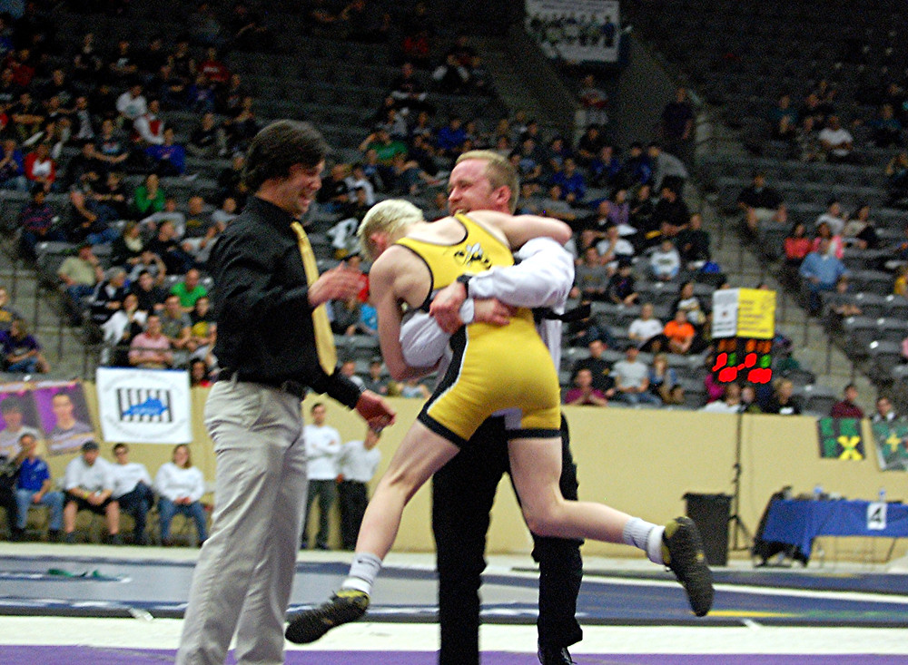 CHASE YOST, an eighth-grader on the Woodford County High School wrestling team, jumped into head coach Rusty Parks Jr.'s arms, while assistant coach Ethan Miller looked on. It was all in celebration of winning a state title at the KHSAA State Wrestling Championships, which were held Friday and Saturday, Feb. 19 and 20, at the at the Alltech Arena at the Kentucky Horse Park. Yost defeated Wayne County's Cagen Wallace 4-2 in overtime in the 106-pound weight class to earn his title. (Photo by Rick Capone)