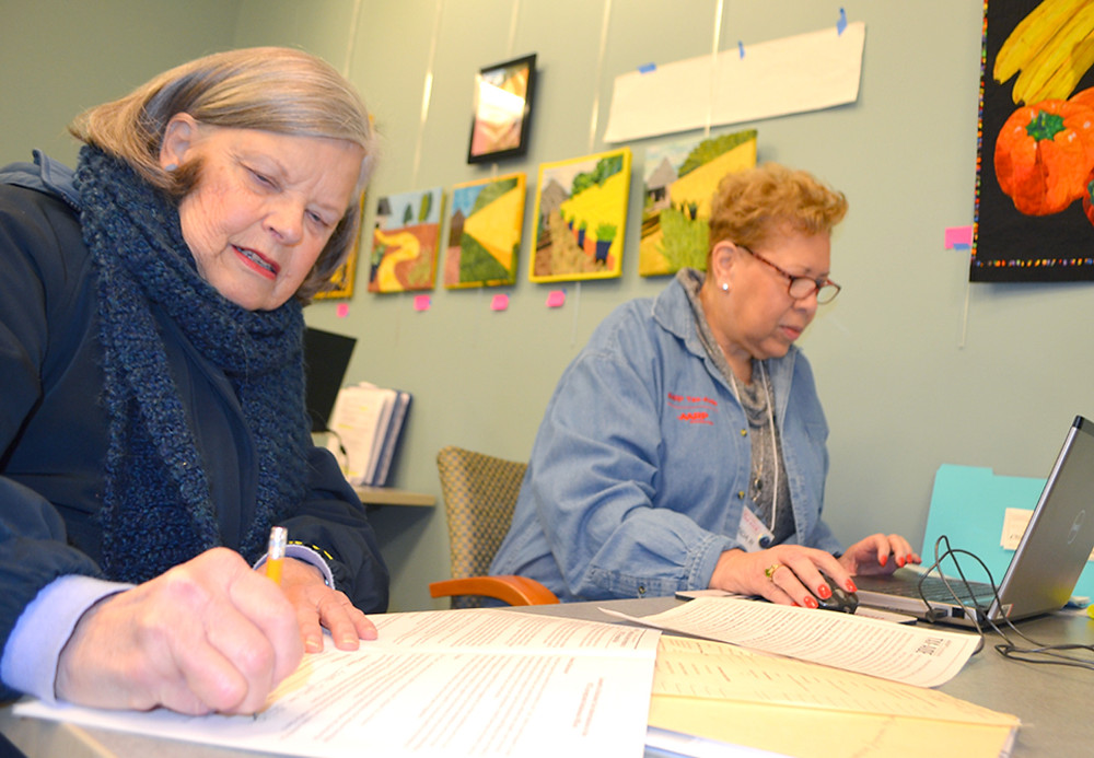 """SUSAN KING, left, who lived in Woodford County for 23 years before moving to Louisville, filed her tax return with the help of Brenda Richards, an AARP Foundation Tax-Aide volunteer. """"I came back here to do my taxes,"""" said King. She and others who came to the Woodford County Library to file their tax returns last Thursday morning said they've used the AARP Foundation Tax-Aide service for several years. (Photo by Bob Vlach)"""