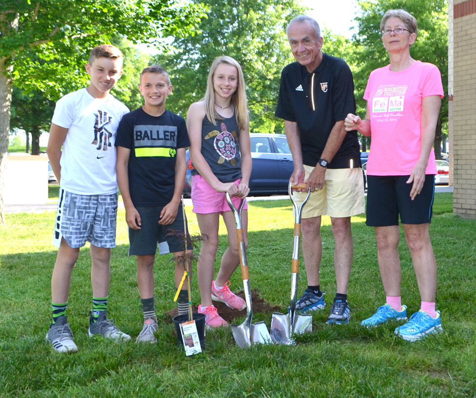 NORTHSIDE ELEMENTARY School fifth-graders, from left, Nolan Asher, Charlie Twehues and Payton Asher joined longtime Woodford County Board of Education Chair Ambrose Wilson IV and his wife, Karen, for a tree planting ceremony outside the Midway school on May 23. (Photo by Bob Vlach)