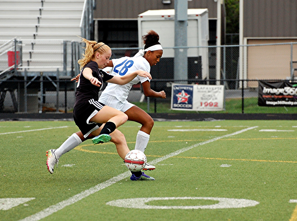 SHELBI MORRISON drives the ball past a Henry Clay defender and went on to score her second goal of the semifinals of the Fayette County Spectacular on Saturday, Aug. 20, at Lafayette. The freshman's two goals helped Woodford come from behind to tie the game, 2-2. However, in the end, Henry Clay won on penalty kicks, 3-2.