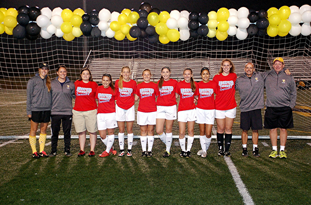 SENIOR CELEBRATION. The Woodford County High School girls' soccer team celebrated senior night prior to its game against Corbin at home on Saturday, Oct. 1. Standing with their coaches, the seniors honored were, left to right, Lyndsay Vance (assistant coach), Abby Baylor (assistant coach), Katie Batman, Emma Sandman, Caitlyn Burdine, Elizabeth Watts, Sydney Smith, Camryn Pictor, Jessel Martinez, Lelia Graf, Brad Turpin, Jr. (head coach), and Craig Boyce (assistant coach). Not pictured: Elena Hitch (assistant coach). (Photo by Rick Capone)