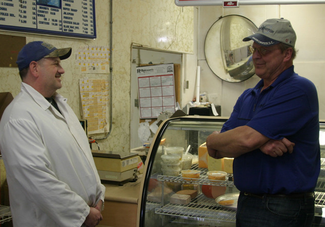 "END OF AN ERA: One week before Moore's Meat and Produce closed, owner John Moore, right, shared a few memories with 25-year butcher Dickie Lacefield. ""I'll find something else to do. I don't know what it is yet,"" Moore said. (Photo by John McGary)"
