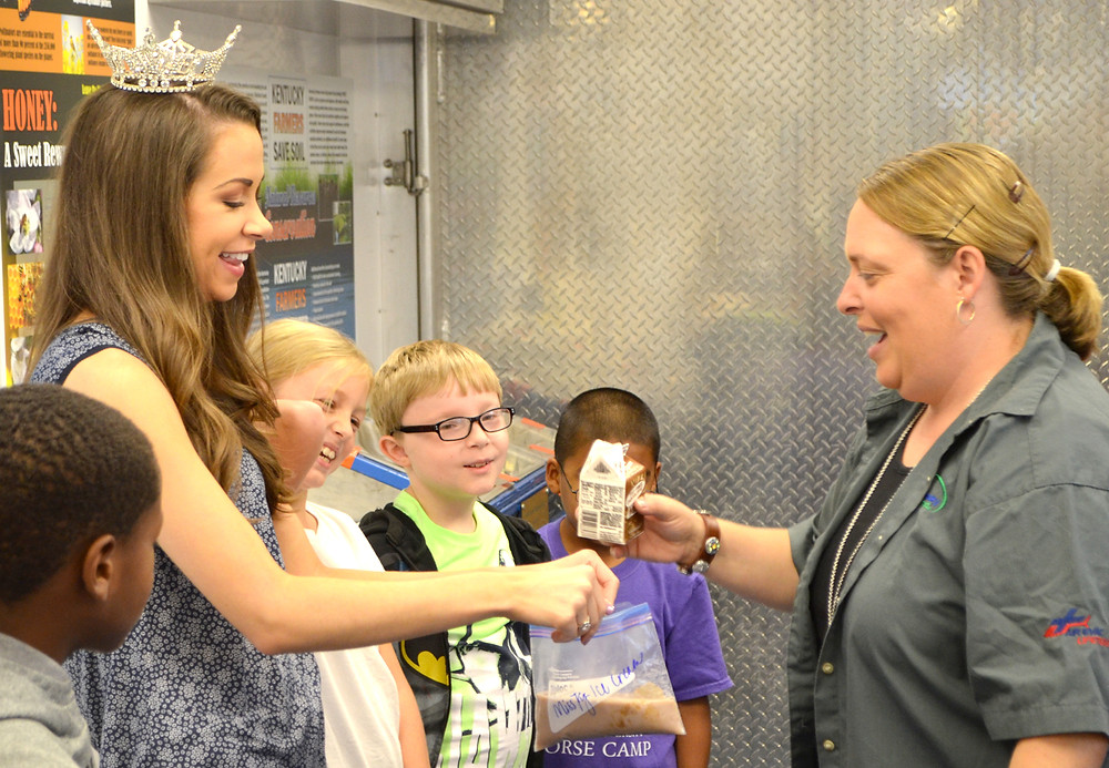 MISS KENTUCKY 2017 Molly Matney, left, helped Brandy Graves, coordinator of the Kentucky Mobile Science Activity Center, give students step-by-step instructions on how to make ice cream with everyday ingredients, including milk and sugar. Fourth-graders Natalie Johnson and Will Hamilton are also pictured. (Photo by Bob Vlach)