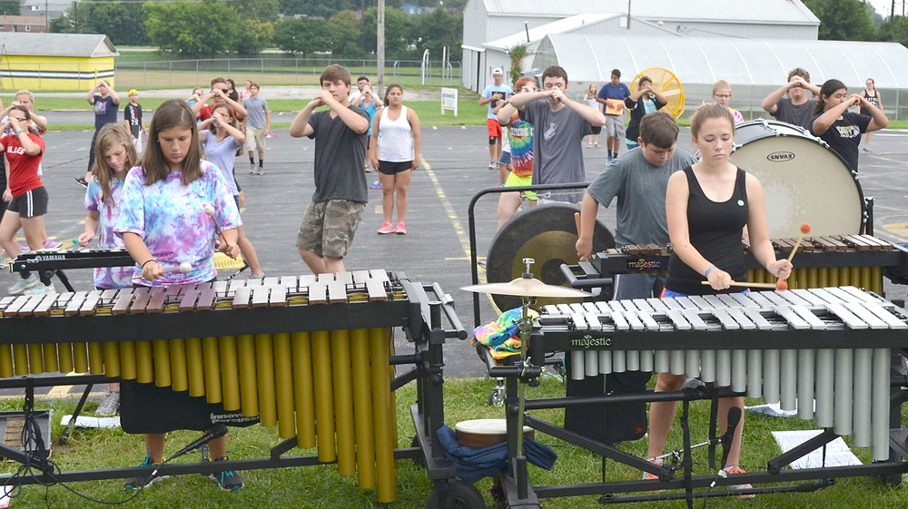 PERCUSSIONISTS in the Woodford County High School marching band played their instruments, while other members of the band worked on their footw