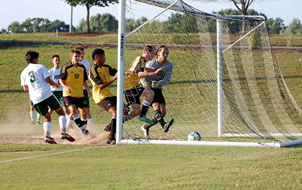 TREVOR WHITE, No. 5, closest to the goal post, came out on top on this scramble for the ball, as he put the ball into the net for a score to tie the game at 1-1 in the first half of Woodford's road game against Western Hills on Thursday, Sept. 8. (Photo by Rick Capone)