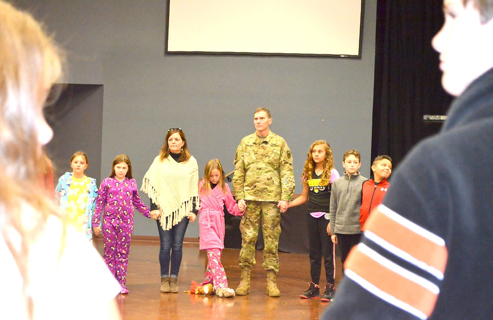 STUDENTS JOINED HANDS with teachers and parents at Woodford Christian School before saying a prayer for veterans and active-duty military men and women. Army National Guardsman Stephen Martin is pictured with his wife, Nicole, and their daughter, Kylie, holding both of her parents' hands. (Photo by Bob Vlach)