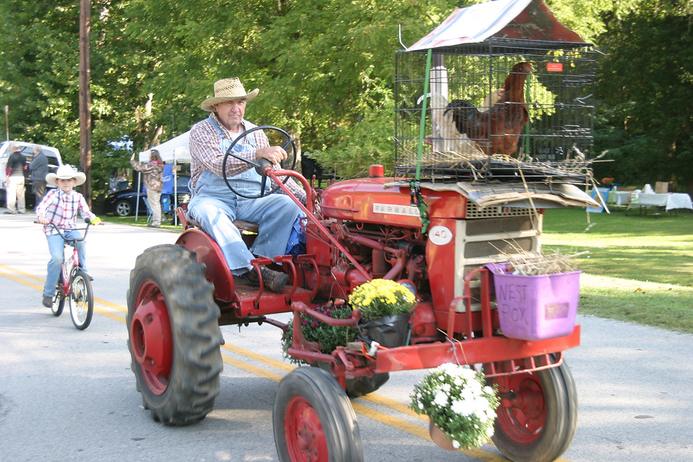 DAVID PENN led the parade at the 37th annual Hillbilly Daze in Millville Saturday. Later, he joked that he couldn't figure out why the hens he'd bought weren't producing eggs. The hens, of course, were roosters. (Photo by John McGary)