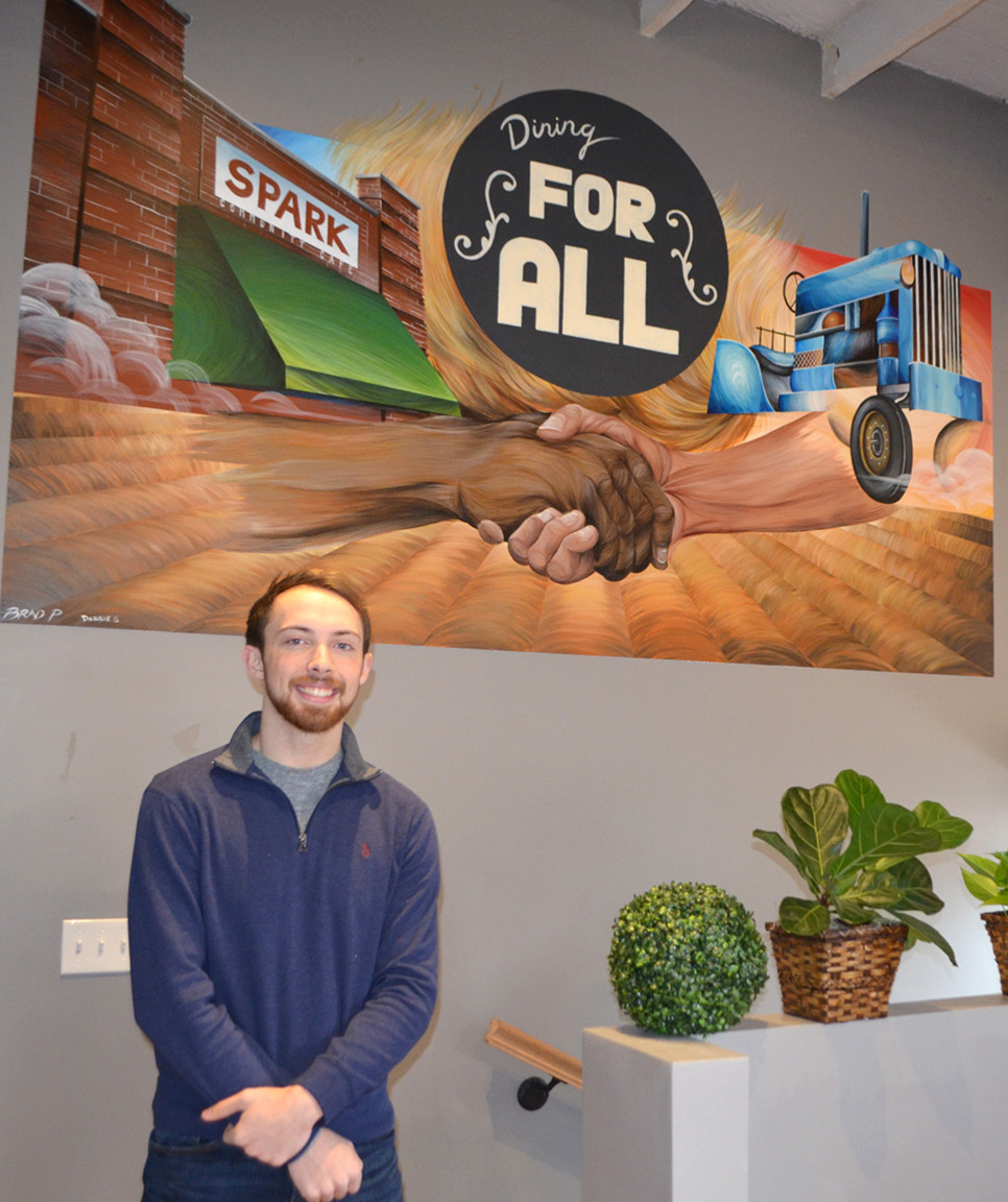 "BRAD PRARIA painted a mural on a dining room wall at Spark Community Café when he came home to Versailles while on summer break from Savannah College of Art and Design. The final element of the mural was two arms – one coming from Spark and the other from the farming community – extended for a handshake. ""That was really what brought it together,"" says Praria. (Photo by Bob Vlach)"