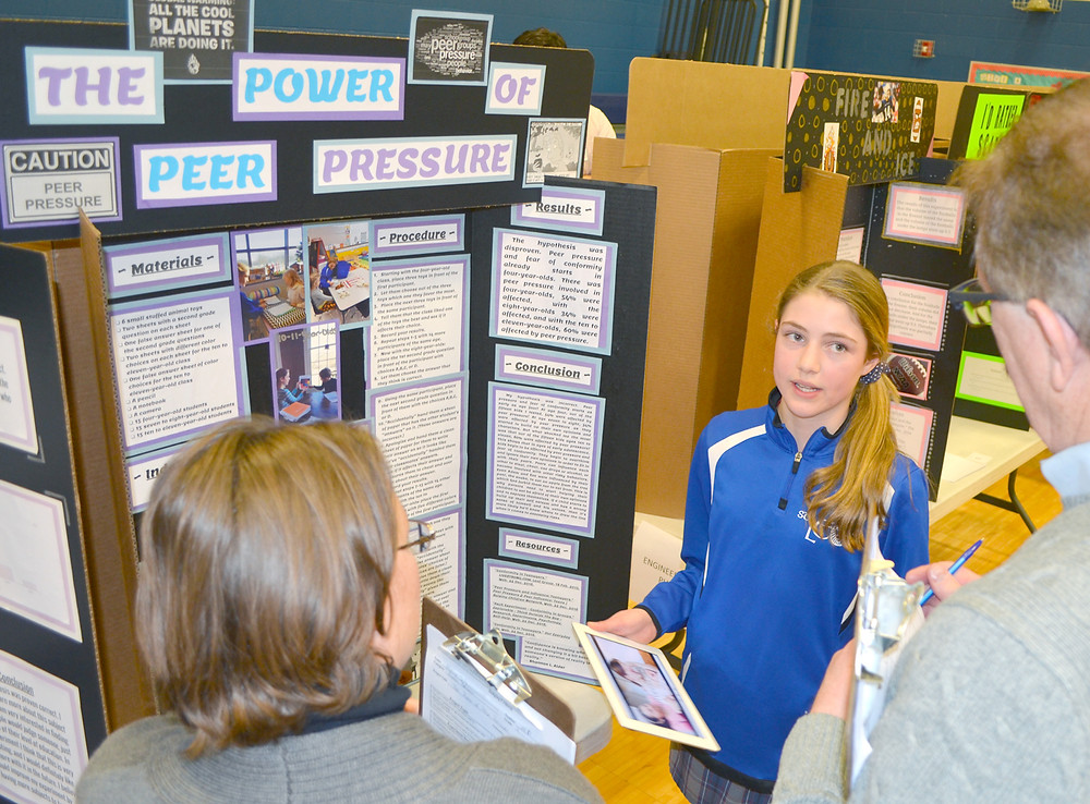 "MONICA SEITZ, an eighth-grader at St. Leo School, used an iPad while explaining her science project, ""The Power of Peer Pressure,"" to judges Nicole Peritore and Michael DiBiasie. (Photo by Bob Vlach)"