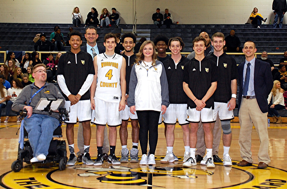 SENIOR CELEBRATION. Prior to the Woodford County High School boys' basketball game against Mercer County in The Hive on Tuesday, Feb. 14, the team honored its seniors in a short ceremony in front of family, teammates and friends. The seniors, with their coaches are, front row, from left, Nick Gibson, Trevor White, Alex Cason, Maddie Hudson, Griffin Mobley, Braxton Caudhill and Josh Brolin; back row, Ryan Wilson (head coach), Keagan Stromberg, Malik Richards, Jerry Skeeter (assistant coach) and Nick Sherman (assistant coach). (Photo by Rick Capone)