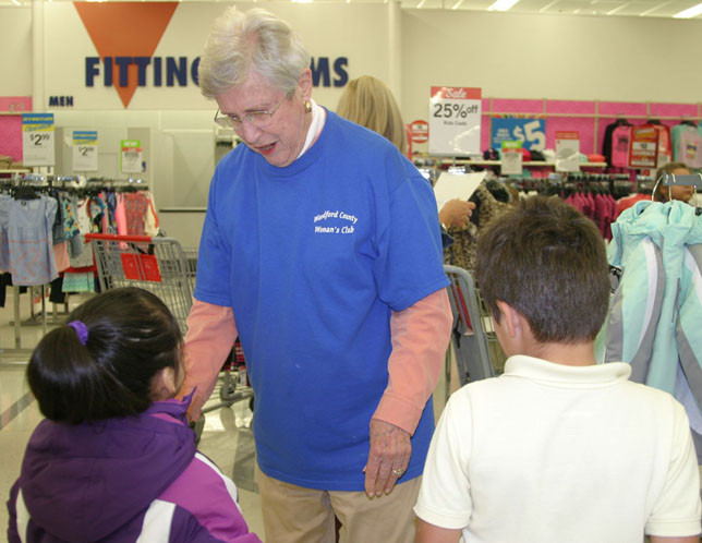 COATS, SHOES AND SOCKS will be given to less privileged children next Monday and Tuesday mornings. This 2017 photo showing Jane Pryor of the Woodford County Woman's Club helping two students from Simmons Elementary was taken in K-Mart, which closed a few months later. The culmination of the annual Woodford County Woman's Club's coats and shoes drive now takes place at Kroger. (File photo by John McGary)
