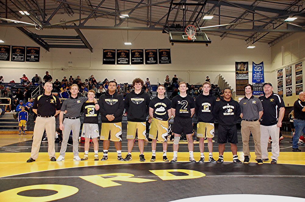 Senior Celebration. During the WCI, the team took a few moments to honor its senior wrestlers. The seniors, along with members of the coaching staff, are, from left, Corey Cardwell (assistant coach), Rusty Parks Jr. (Head Coach), Tucker Hurst, Helio Reyes, Kyle Hamlin, Matthew Fallon, Michael Eldridge, Dermot Cunningham, Emir Bernabe, Ethan Miller (assistant coach) and Robert Tucker (assistant coach). (Photo by Rick Capone)