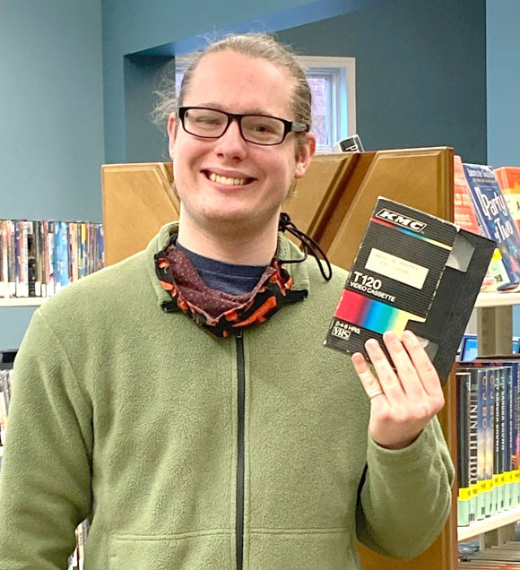 """NOLAN GREENE, a library assistant, is pictured with a VHS tape he uncovered while helping clean the Woodford County Library's basement in December. Greene and a friend since sixth grade at St. Leo School, Robert Smith, digitized the videotape of """"Kentucky Life in Woodford County,"""" which was produced by WLEX-TV in 1989. With LEX18's permission, the library has posted the hour-long video on its Facebook page. (Photo submitted)"""