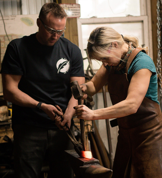 "JENNIFER LYDDANE, shown here with her husband Jody in their backyard shop, is a contestant on The History Channel's ""Forged in Fire"" show for the second time. (Photo by Hannah Segura)"