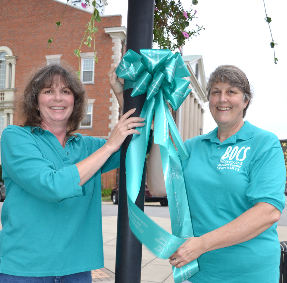 "JUDY KORBY, left, and Sue Jacobs were among a group of Woodford County volunteers who were busy hanging teal-colored bows along Main and Lexington streets in downtown Versailles last Wednesday, Aug. 31. ""Turn The Towns Teal"" happens in communities across the country every September to raise awareness about ovarian cancer. (Photo by Bob Vlach)"