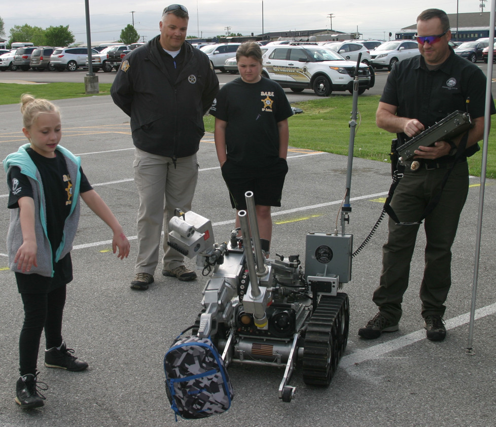 "CHELSEY GLOVER prepares to retrieve a backpack from a Kentucky State Police Bomb Squad robot dubbed ""Jarvis"" at Friday's DARE Fun Day. From left are Glover, Woodford Sheriff's Deputy Bo Morgan and his daughter, Shelby, and KSP Bomb Squad Commander Jim Adkins. (Photo by John McGary)"