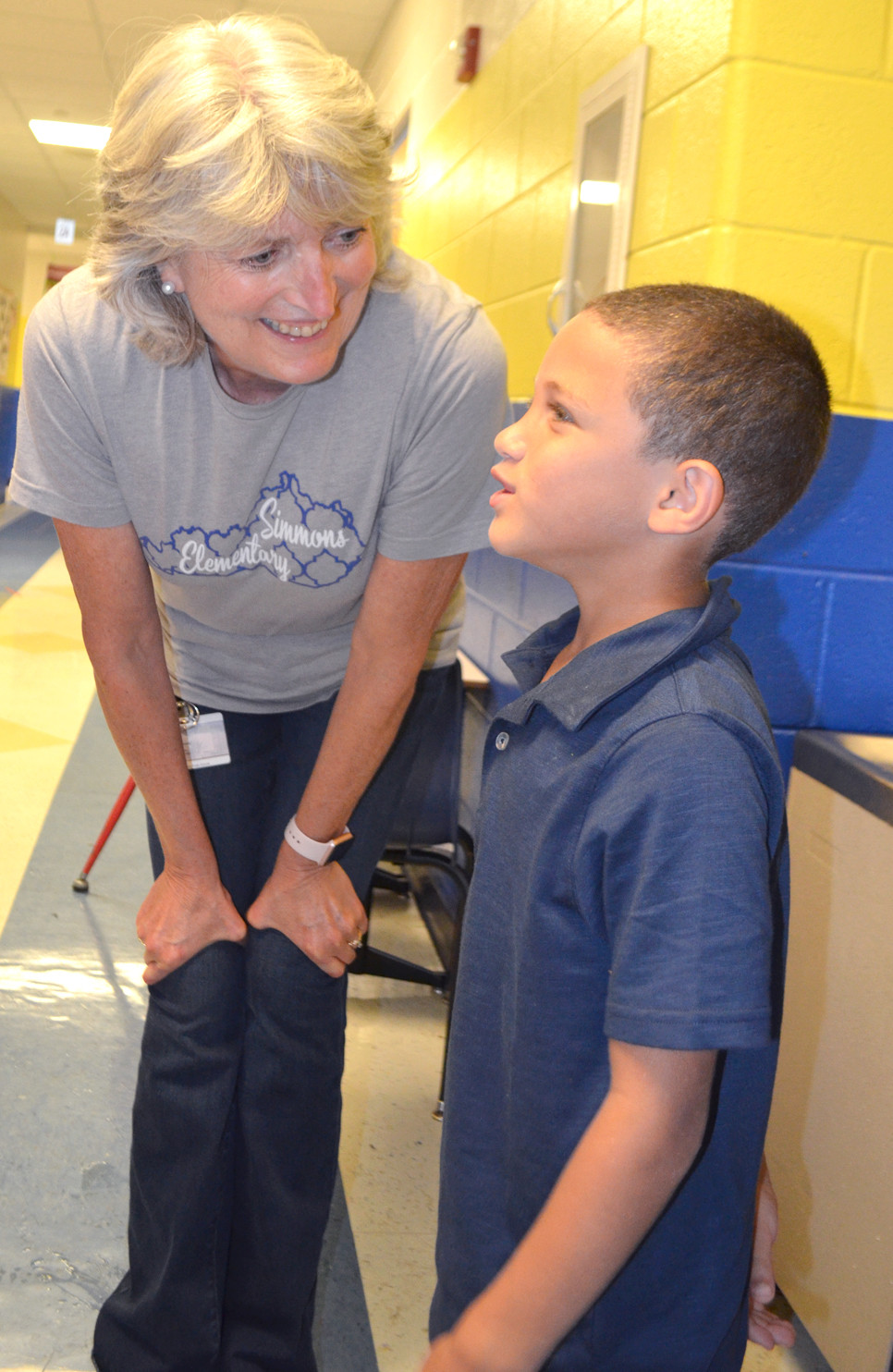 """BARB RUSH talked to kindergartner Levi Johnson outside their classroom at Simmons Elementary School recently. """"Relationships are so important with them,"""" says Rush, who began her 19th year at Simmons in August. (Photo by Bob Vlach)"""