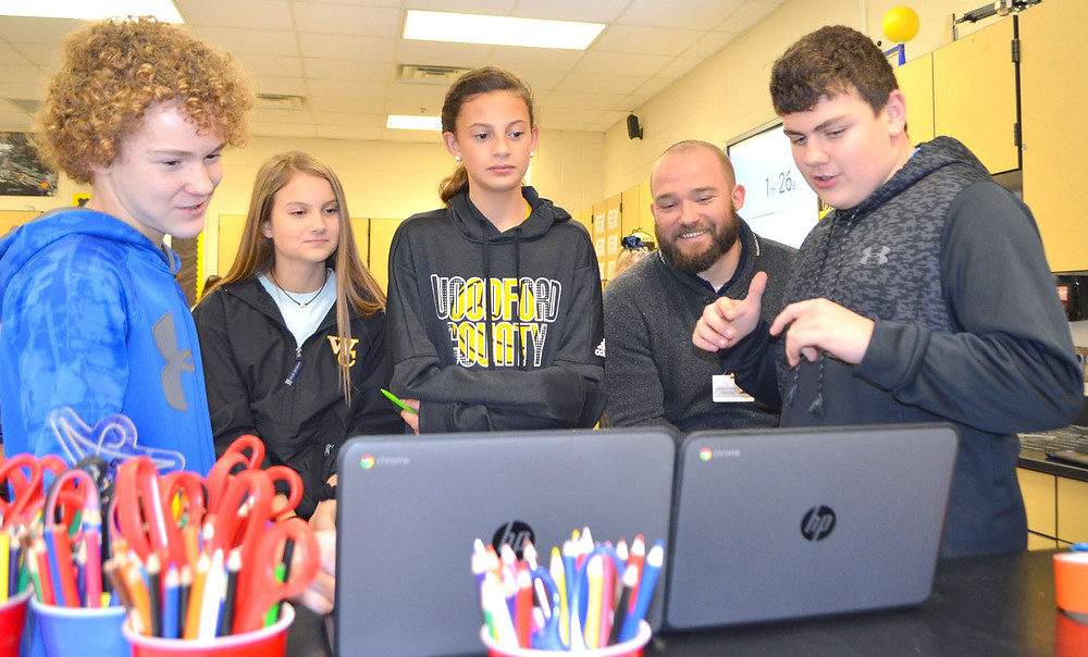 SEVENTH-GRADE SCIENCE teacher Kyle Norton says he wants to foster his students' curiosity about their world so they'll ask questions. From left are Zack Meckley, Liz Hamm, Maddie Loveless, Norton and Jackson Cabell. (Photo by Bob Vlach)