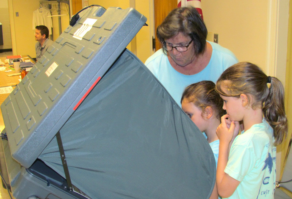 THIS SCENE FROM the May 2018 primary will be very rare in the June 23 primary, when most voters will be casting their ballot via mail (though ballots can also be dropped off in a secure, video-monitored ballot box on the first floor of the county courthouse). Two years ago, Linda Tilghman, accompanied by granddaughters, from left, Sloane Coyle and Ella Coyle and, not seen, Mallory Coyle, cast her votes in the basement of the courthouse. (File photo by John McGary)