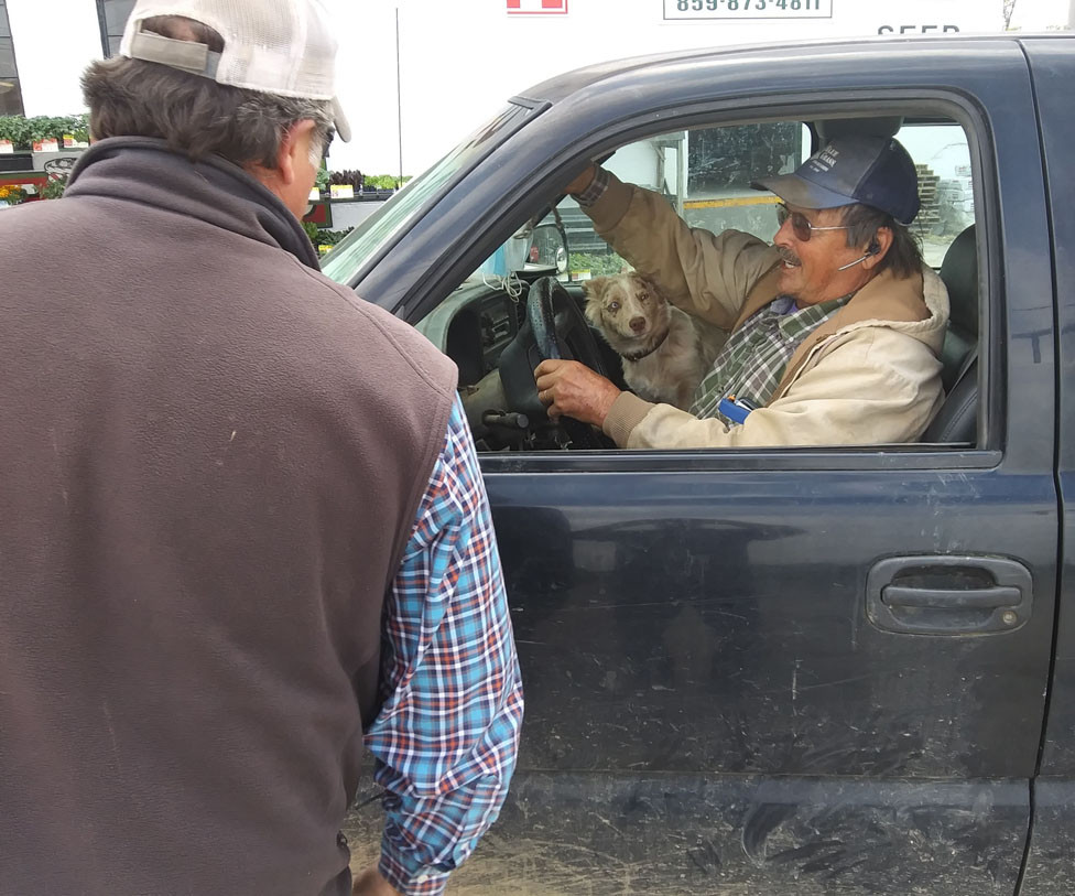 WOODFORD FEED employee Greg Dotson shared a chuckle last Friday with longtime customer Vernon Leach, who'd come to purchase parts for cattle panels. Looking on was Leach's Australian shepherd pup,  Lady. Leach said he's been coming to the store all his life. (Photo by John McGary)