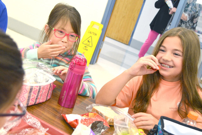 SOUTHSIDE ELEMENTARY School third-graders Gabby Valentine, left, and Bailee Christopher ate lunch Monday. An expansion of the school's cafeteria and kitchen will shorten those times, currently 10:45 a.m. to 1:15 p.m., when lunches are served. Southside's enrollment of 564 students is the highest among four public elementary schools in Woodford County Public Schools. (Photo by Bob Vlach)