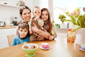 Mother and children sitting at table