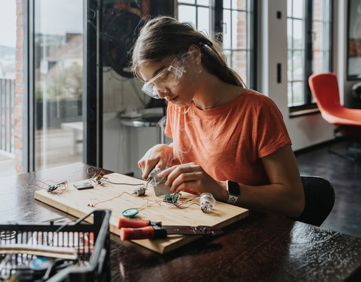 Teenage girl working with soldering bolt