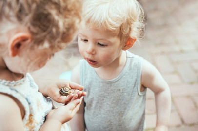 Two kids examining a snail in its housing