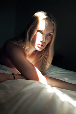 Woman with stroke of sunlight over her face