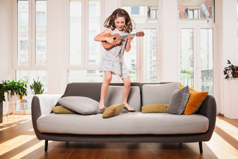 Happy child playing Ukulele on a couch