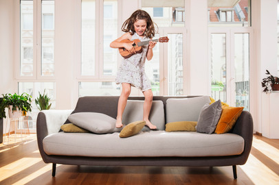 Happy kid playing ukulele while jumping on couch