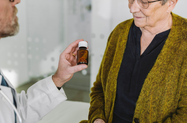 Pill bottle being presented to elderly patient