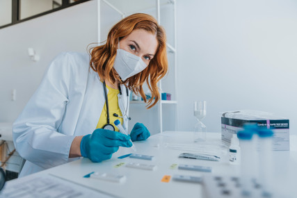 Woman engaged in processing Covid-19 rapid tests