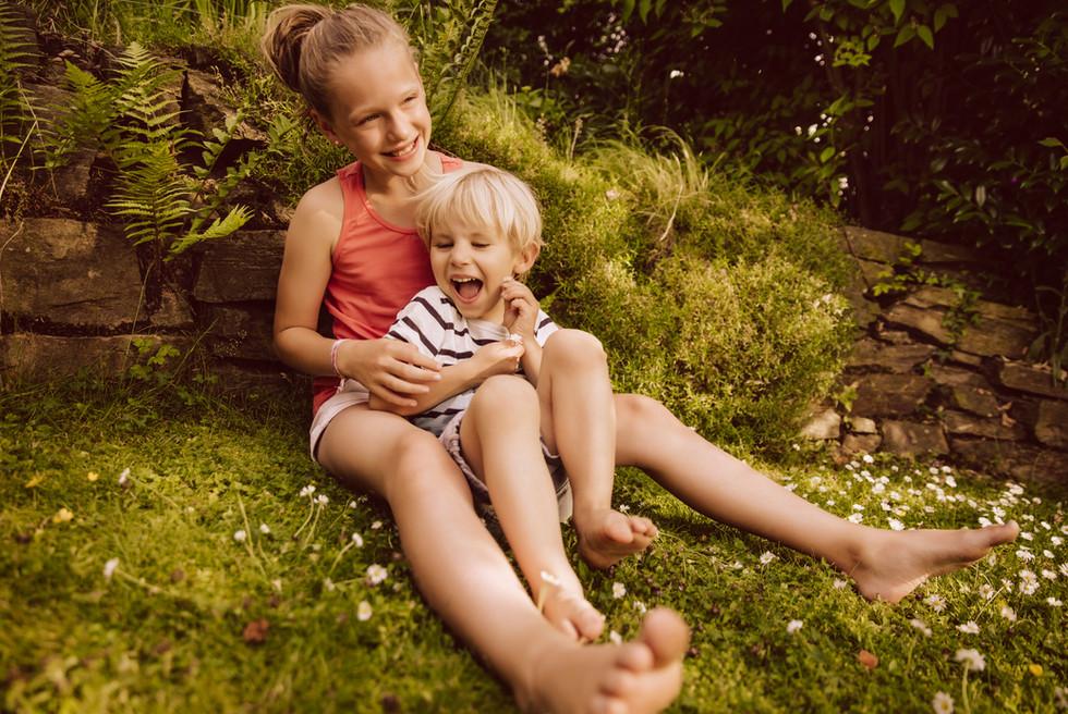 Two kids cuddling in the garden