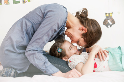 Mother and child cuddling on bed