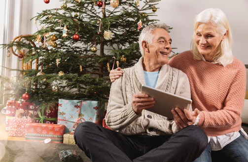 Happy elderly couple in front of Christmas tree