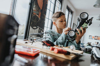 Boy tinkering with his remote-controlled car