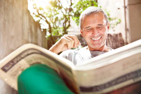 Happy senior reading newspaper