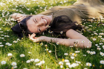 Young woman enjoying summer in grass with daisies