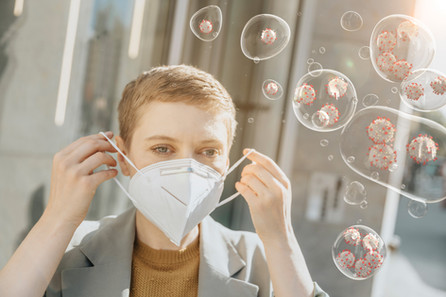 Woman putting on a medical mask against aerosoles containing virus
